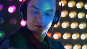 Ein DJ klatscht, nachdem es seine Kopfhörer beseitigt hat stock footage