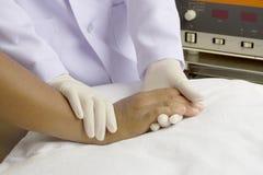 Ein Doktor überprüft Hand des Patienten Lizenzfreies Stockfoto