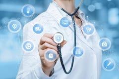 Ein Doktor berührt einen digitalen Entwurf von den drahtlosen Verbindungen, die kleine Bereiche mit medizinischen Ikonen nach inn lizenzfreie stockfotografie