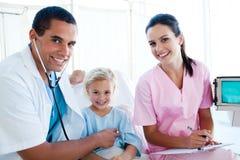 Ein Doktor, der den Impuls auf einem kleinen Mädchen überprüft Lizenzfreies Stockbild