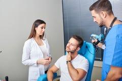 Ein Doktor, der den Patienten in den Schmerz überprüft lizenzfreie stockfotos