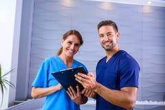 Ein Doktor, der Details eines medizinischen Verfahrens mit seinem Assi bespricht Stockbilder