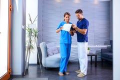 Ein Doktor, der Details eines medizinischen Verfahrens mit seinem Assi bespricht Lizenzfreies Stockbild