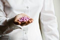 Ein Doktor, der eine Handvoll der Vitaminergänzung anhält Stockbilder
