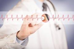 Ein Doktor, der eine Herzpille hält Lizenzfreies Stockfoto