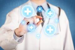 Ein Doktor, der eine Pille mit Kreuzen zeigt Lizenzfreies Stockfoto