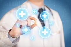 Ein Doktor, der eine Pille mit Kreuzen zeigt Lizenzfreie Stockfotografie