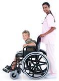 Ein Doktor, der einen Patienten in einem Rollstuhl trägt Stockbild
