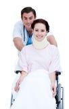 Ein Doktor, der einen Patienten in einem Rollstuhl trägt Lizenzfreies Stockbild