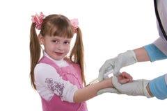Ein Doktor, der kleinem Mädchen eine Einspritzung gibt lizenzfreie stockbilder