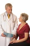 Ein Doktor mit seinem Patienten, der Anmerkungen betrachtet Lizenzfreie Stockfotos