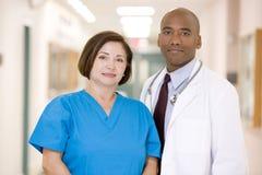 Ein Doktor und eine Krankenschwester, die in einem Krankenhaus-Flur stehen Stockbilder