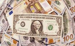 Ein Dollar über einer fünfzig Euroanmerkung und hundert Dollar Stockbild