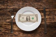 Ein Dollar auf einer weißen Platte nahe bei Gabel und Messer Stockbilder