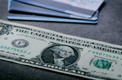 Ein-Dollar-Banknoten auf einer schwarzen Tabelle mit Kreditkarten Bargeld-Amerikaner-Dollar Geometrische Verzierung auf einem alt Stockbild