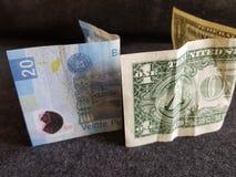 ein Dollarschein und 20 Pesos Mexiko-Rechnung Lizenzfreies Stockfoto