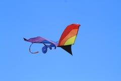 Ein Drachen, der über einen blauen Himmel fliegt Lizenzfreie Stockfotografie