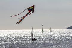 Ein Drachen fliegt hoch über die Yachten, die weg vom Beachy Kopf nahe Eastbourne in Ost-Sussex, England segeln lizenzfreie stockbilder
