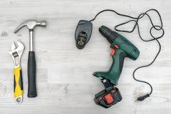Ein drahtloses Bohrgerät, es Ladegerät neben einem Hammer und ein Schlüssel auf Holztischhintergrund Lizenzfreies Stockfoto