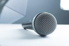 Ein drahtloses Mikrofon, das auf einer weißen Tabelle liegt Vor dem hintergrund der Studioausrüstung weiche Kästen stockbild