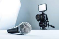 Ein drahtloses Mikrofon, das auf einer weißen Tabelle vor dem hintergrund der DSLR-Kamera zu geführtem Licht liegt lizenzfreies stockfoto