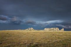Ein dunkler und stürmischer Himmel hinter einer felsigen Kante auf dem Grasland Lizenzfreie Stockfotografie