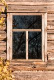 Ein dunkles Fenster in einem Blockhaus und ein Baumast mit Blättern Stockfotografie
