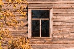 Ein dunkles Fenster in einem Blockhaus und ein Baumast mit Blättern Lizenzfreies Stockbild