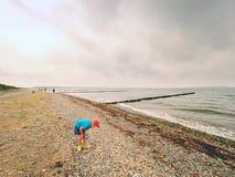 Ein durchdachter blonder Junge, der auf Strand nahe Wasser bleibt Langer steiniger Strand mit hölzernem Wellenbrecher Lizenzfreie Stockfotos