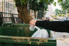 Ein Durchschnittsbürger wirft eine Plastikflasche in einen Behälter mit Abfall Sorgfalt für die Umwelt Eco freundlich Tourist stockbilder