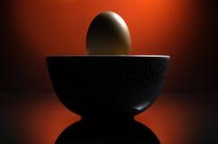 Ein Ei mit einem drastischen roten Hintergrund. Lizenzfreie Stockfotos