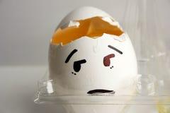Ein Ei mit einem Gesicht Konzept von Kopfschmerzen Lizenzfreie Stockbilder