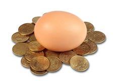 Ein Ei und Münzen Stockbild