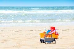 Ein Eimer und Sandspielwaren während der Kinderspielzeit am Strand Lizenzfreies Stockfoto