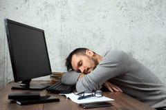 Ein an einem Tisch im Büro, die nicht Mann, ein Mann sitzen und, müder Blick arbeiten Das Konzept der Büroarbeit, Trägheitsermüdu lizenzfreie stockfotos