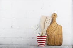 Ein einfaches Küchenstillleben gegen eine weiße Backsteinmauer: Schneidebrett, Ausrüstung kochend, Keramik horizontal Lizenzfreies Stockfoto
