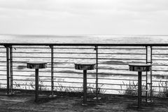 Ein einfarbiges Bild von drei Stühlen auf der Küste Lizenzfreies Stockfoto