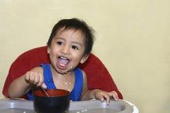 Ein einjähriges Baby, das lernt, allein lächeln zu essen glücklich aber unordentlich Stockbild