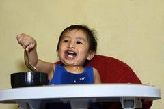 Ein einjähriges Baby, das lernt, allein lächeln zu essen glücklich aber unordentlich Lizenzfreie Stockbilder