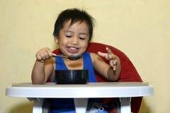 Ein einjähriges Baby, das lernt, allein lächeln zu essen glücklich aber unordentlich Lizenzfreies Stockbild
