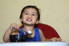 Ein einjähriges Baby, das lernt, allein lächeln zu essen glücklich aber unordentlich auf dem Baby zu Hause speist Stuhl Stockbilder