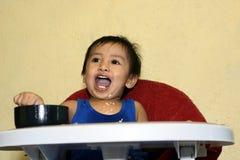 Ein einjähriges Baby, das lernt, allein lächeln zu essen glücklich aber unordentlich auf dem Baby zu Hause speist Stuhl Lizenzfreies Stockbild