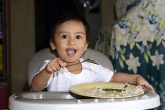 Ein einjähriges Baby, das lernt, allein lächeln zu essen glücklich aber unordentlich auf dem Baby zu Hause speist Stuhl Stockfoto