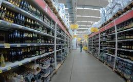 Ein Einkaufswagen ist ein Übergang zwischen den Regalen eines Supermarktes Lizenzfreie Stockfotos