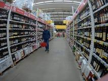 Ein Einkaufswagen ist ein Übergang zwischen den Regalen eines Supermarktes Lizenzfreie Stockfotografie