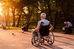 Ein einsamer alter Mann, der in den Blicken eines Rollstuhls bei einem schönen Sonnenuntergang im Park sitzt Lizenzfreies Stockbild