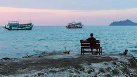 Ein einsamer Mann, der auf dem Seepier an der Dämmerung sitzt Lizenzfreies Stockbild