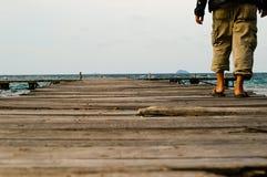 Ein einsamer Mann, der in hölzernen Hafen geht Lizenzfreies Stockbild