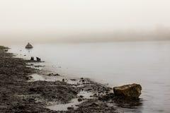Ein einsamer Mann in einem Gummiboot auf dem Fluss früh morgens, stockbild