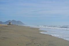 Ein einsamer Strand mit Bergen Lizenzfreies Stockfoto